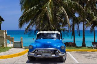 Amerikanischer blauer Oldtimer parkt am Strand unter Palmen in Varadero Cuba - Serie Cuba Reportage