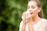 Frau hat Schnupfen und niest