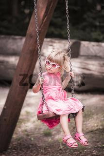 Little blond girl on a swing