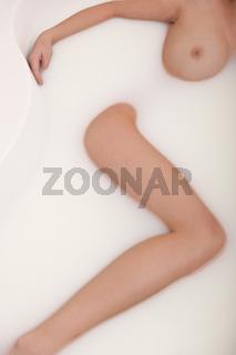 Body care: Woman having milk bath in bathtub