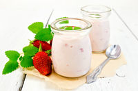 Yogurt with strawberries in jar on parchment and board