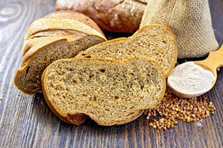 Bread buckwheat with cereals and flour in spoon on board