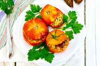 Tomatoes stuffed with bulgur and parsley in plate on board top