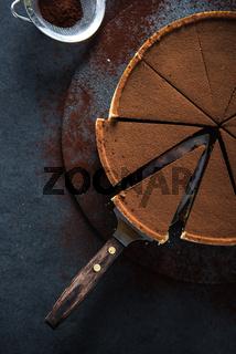Sliced chocolate tort on dark background
