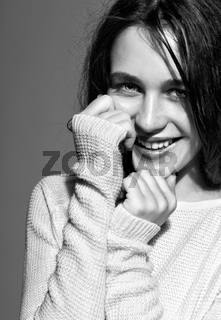 Portrait of smiling happy young brunette woman portrait in white fashion female pullover