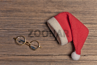 Santa red hat and spectacles on wooden background, holiday Christmas