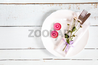 White empty plate, pink chrysanthemum flowers, two pink candles, napkin, fork and knife tied with a violet ribbon on light wooden background.