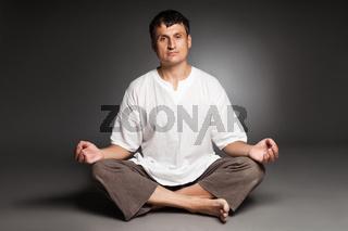 Peaceful man meditating isolated over dark