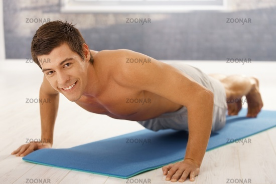 Goodlooking guy doing push up in gym