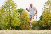 Senior macht einen Luftsprung beim Wandern