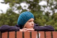 Mädchen stützt sich auf einer Mauer auf