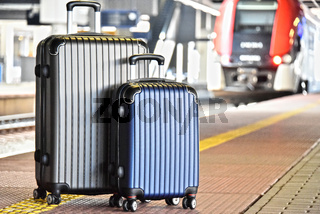 Two plastic travel suitcases on the railroad platform
