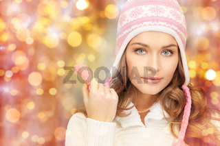 happy woman in winter hat over lights