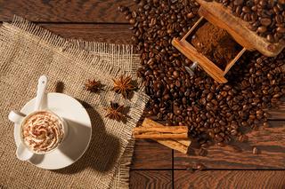 Coffee cup, star anise, cinnamon sticks and coffee-beans
