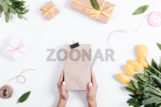 Female hand holding a paper bag with a gift on a table near the tulips, ribbons and boxes