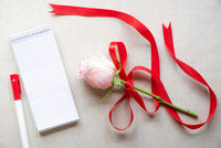 Blank notebook and a rose with red ribbon