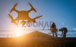 Silhouette of Unmanned Aircraft System (UAV) Quadcopter Drone In The Air Over Building Under Construction.