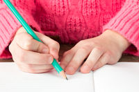 Child hand with pencil starting to write