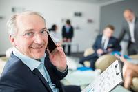 Erfahrener Berater  telefoniert mit Smartphone