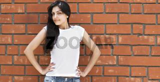 Brunette woman at brick wall