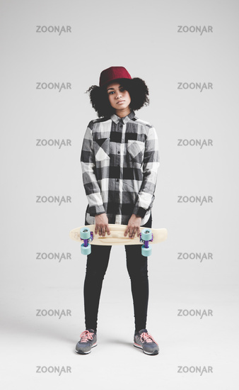 Smiling african teenager girl with yellow skateboard. Isolated on white background