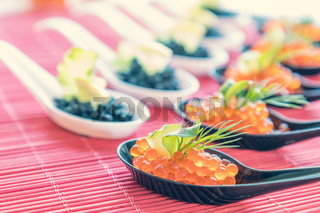 Delicious red and black caviar fish close-up in white and black spoons on white table. Beautifully decorated catering banquet table.