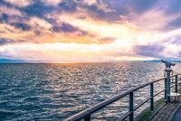 Binocular on a lake shore at sunset