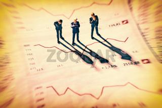 Geschäftsmänner und Grafiken mit Börsenkursen