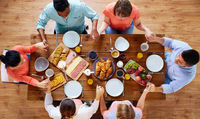 group of people at table praying before meal