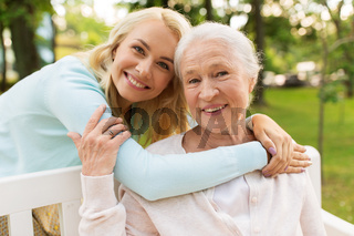 daughter with senior mother hugging on park bench