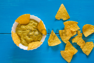Nachos chips and salsa guacamole over a blue background