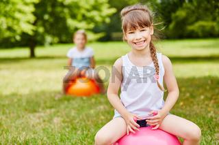 Mädchen auf Hüpfball in den Ferien