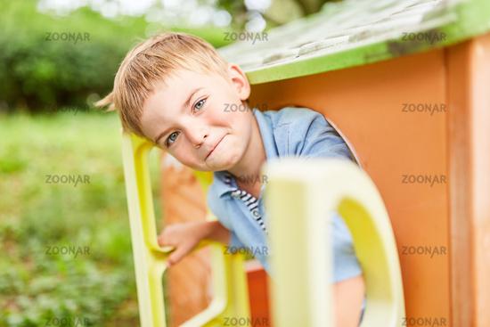 Junge blickt schelmisch aus dem Spielhaus