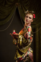 Beautiful young woman as geisha with candle