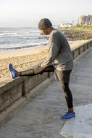 Jogger Stretching on Promonade by beach