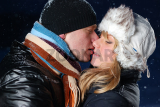 young couple is kissing at winter evening