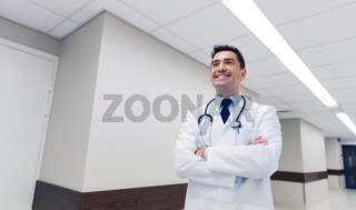 smiling doctor in white coat at hospital