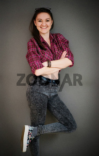 Vertical portrait of brunette girl with glasses wearing casual clothes background gray wall.