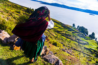 Indigenous inca woman thinking and looking Over sunny lake Titicaca, Peru. South America