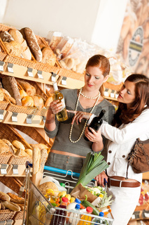 Grocery store: Two young women choosing wine