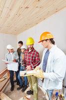 Team mit Bauplan und Checkliste
