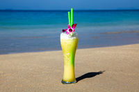 Big Glass Of Cocktail With Two Straws And Flower On The Beach Sand