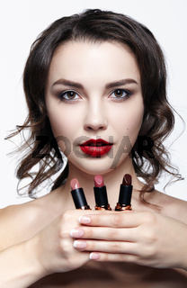 Portrait of young brunette woman. Girl with lipstick in hand. Female lips beauty makeup concept