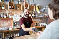 man or waiter with card reader and customer at bar