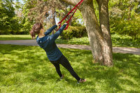 Frau macht Suspension Sling Training im Park