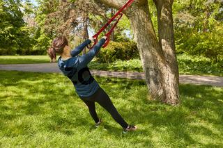 Frau macht Suspension Sling Training im Park