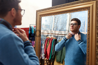 man looking at mirror at vintage clothing store