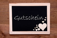 Blackboard With Wooden Hearts, Gutschein Means Voucher