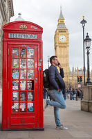 Man talking on mobile phone, red telephone box and Big Ben. London, England