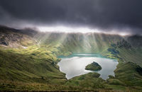 sunrays through clouds over alpine lake